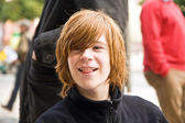 Boy with long red hair pokes his tongue as a joke and smiles — Stock Photo