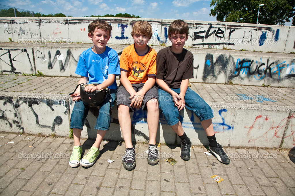 Three friends relaxing and sitting on a concrete bench at the skate park — Stock Photo #6001442