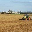 Traktor is running on the acre plowing the earth in golden light - Стоковая фотография