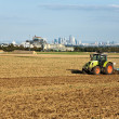 Traktor is running on the acre plowing the earth in golden light - Stock Photo