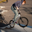 Young boy with red hair is jumping with his bike at the skate park — Foto Stock