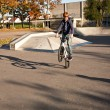 Stock Photo: Boy with red hair is jumping with his BMX Bike at skate park