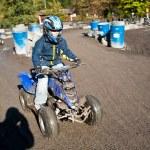 niño le encanta correr con una moto quad en el lodo cuádruple — Foto de Stock
