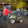 Child loves to race with a quad bike at the muddy quad track — ストック写真