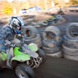 Foto de Stock  : Child loves to race with a quad bike at the muddy quad track