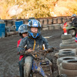 Stock Photo: Child loves to race with a quad bike at the muddy quad track
