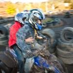 dítě miluje závodit s čtyřkolku na rozblácené trati quad — Stock fotografie