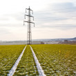 Stock Photo: Electrical tower in winter on flatland with marks of car in field