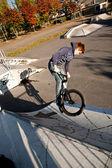 мальчик с рыжими волосами прыжки с его велосипед в скейт-парк — Стоковое фото