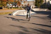 红头发的男孩他在滑板公园的小轮车自行车与跳 — 图库照片