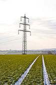 Electrical tower in winter on flatland with marks of car in field — Stockfoto