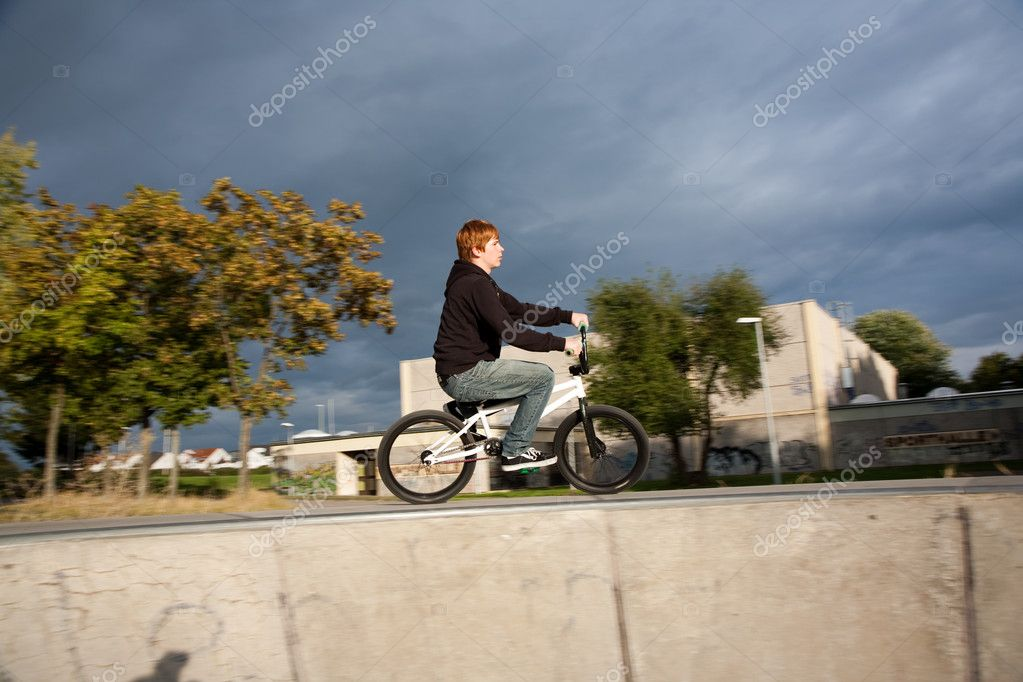 Joung red haired boy is jumping with his BMX Bike at the ...