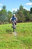 Мальчик, гонки с его велосипед в открытой местности — Стоковое фото