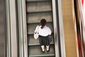 Student op de moving trap in school jurk — Stockfoto