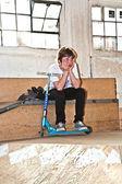Wyczerpany chłopiec ma odpoczynku z jazda na skuterach — Zdjęcie stockowe