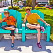 Two brothers are sitting on a art deco park bench in south Miami — Stock Photo