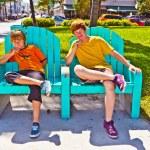dva bratři se sedí na lavičce v parku ve stylu art deco v Jižní miami — Stock fotografie