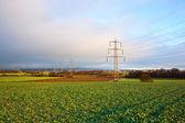 Elektriska tower i landskap med mörka moln — Stockfoto