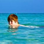 Boy enjoys the beautiful clean sea and has fun — Stock Photo