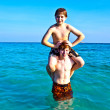 Foto Stock: Brothers are enjoying the clear warm water at the beautiful beach