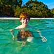 Stock Photo: Red haired boy enjoys the crystal clear water in the sea