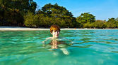 Red haired boy enjoys the beautiful clean sea and has fun — Stock Photo