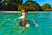 Red haired boy enjoys the crystal clear water in the sea — Stock Photo
