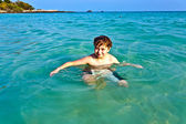 Young boy enjoys the clear water of the ocean — Stock Photo