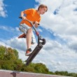 Stock Photo: Cute boy going airborne with his scooter