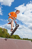 Cute boy going airborne with his scooter — Stock Photo