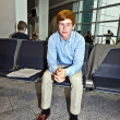 Boy waiting in the gate at the airport for the call of boarding - Stock Photo