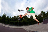 Boy jumping in the air with his scooter — Stock Photo