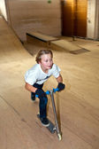 Boy is scooting with his scooter in a indoor hall — Stock Photo