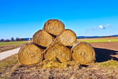 Bale of straw in foil on field with blue sky — Stock Photo