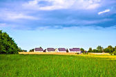 Noise protection wall with field and houses — Stock Photo