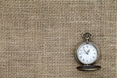 Pocket watch on canvas fabric — Stock Photo