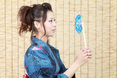 Japanese woman in traditional clothes of kimono with pinwheel — Stock Photo