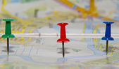 Red, blue and green pushpins on map — Stock Photo