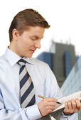 Business man holding a clipboard with corporate buildings — Stockfoto
