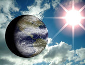 3D earth with blue sky and sun lens flare on the background — Stock Photo