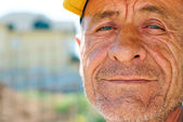 Old wrinkled man with yellow cap — Stock Photo
