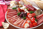 Platter of antipasto, with crusty bread. A mixture of salami, prosciutto, bocconcini, grilled peppers stuffed with goat's cheese, eggplant, tomatoes, and olive — Stock Photo