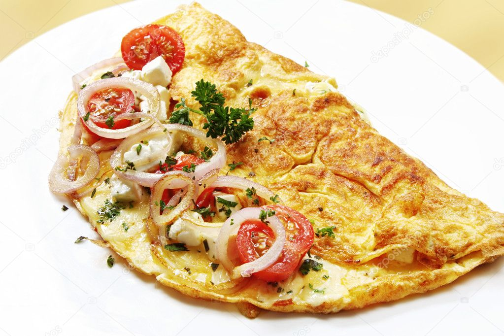 Omelette with cherry tomatoes, red onion, mozzarella, goat's cheese and herbs.  A delicious, nutritious breakfast.  Stock Photo #5526507
