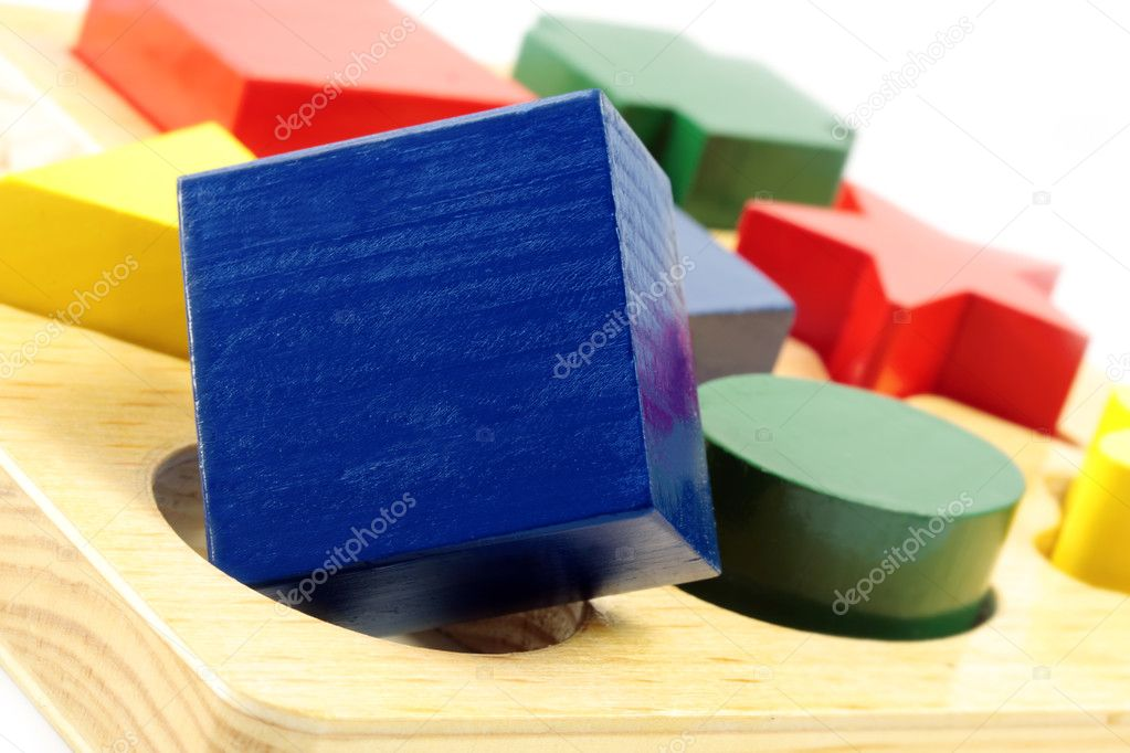 Square peg in a round hole.  Wooden block shapes, with square block over round hole. — Stock Photo #5527033