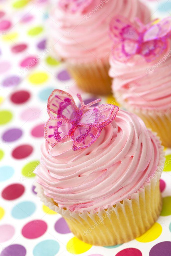 与粉红色糖霜和闪亮的蝴蝶,在圆点背景的香草蛋糕.
