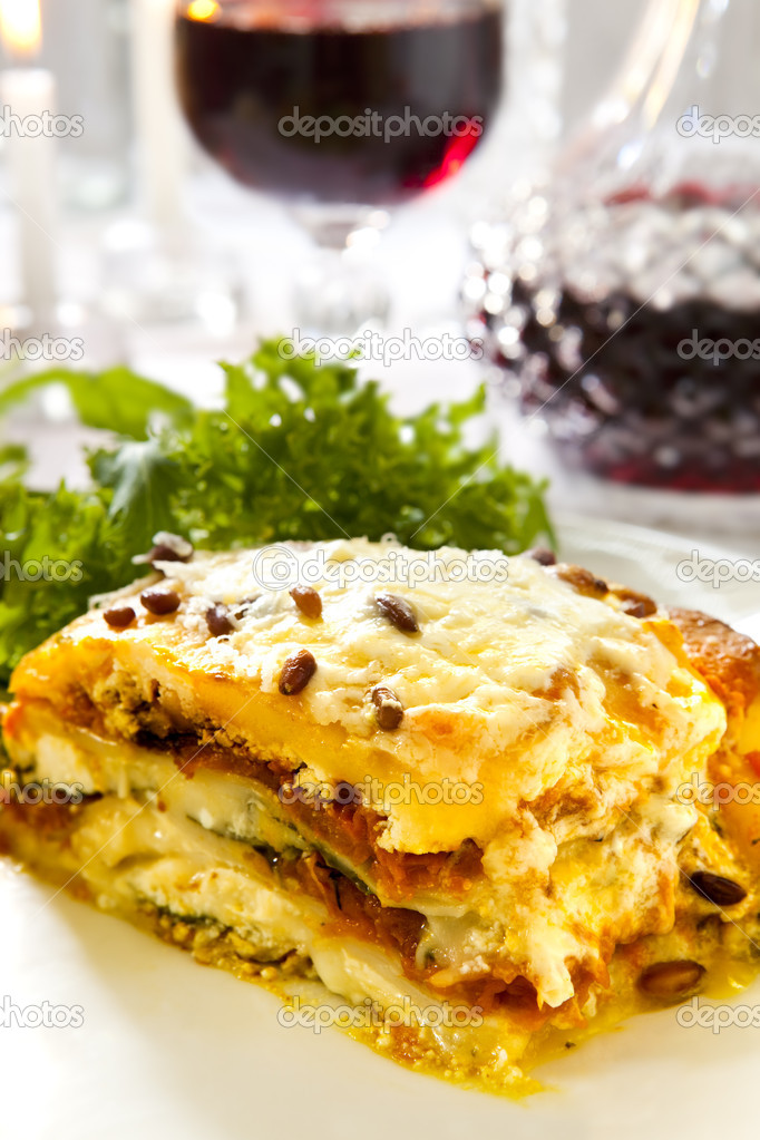 Vegetarian lasagne topped with toasted pine nuts, with salad and red wine.  Shallow depth of field.  Stock Photo #5534160