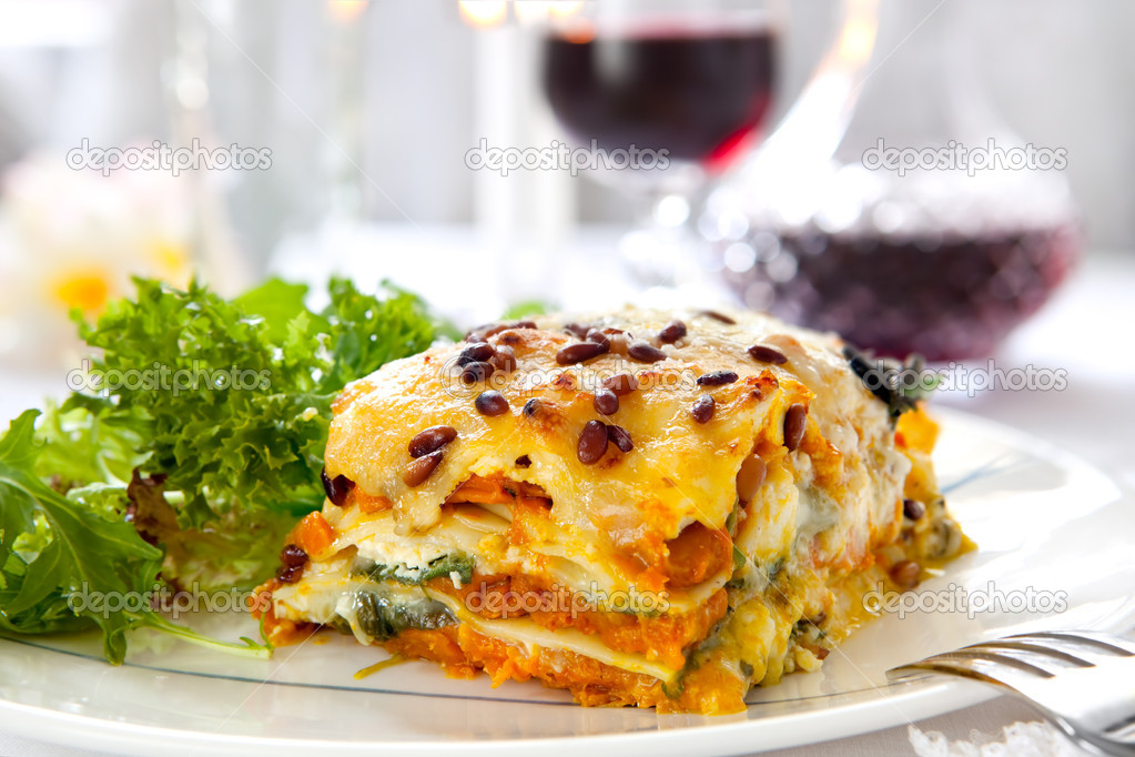 Vegetarian lasagne topped with toasted pine nuts and melting cheeses.  With salad and red wine. — Stock Photo #5534166