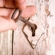 Old key opening the door — Stock Photo