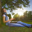 Beauty girl with laptop in park — Stock Photo