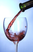 Wine glass and wine puring from bottle — Stock Photo